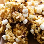 S'more Popcorn... This is coated in the most delicious ooey-gooey marshmallow-caramel and then garnished with graham cracker crumbs, mini chocolate chips and more mini marshmallows for the perfect finishing touch! It is one highly delicious and addictive snack!