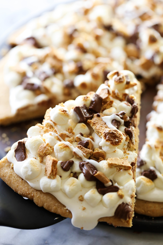 This S'more Cookie Pizza begins with a graham cracker cookie that is topped with marshmallow cream, mini marshmallows, chocolate and crushed graham crackers. It is a delicious, show-stopping dessert that is perfect for special occasions!
