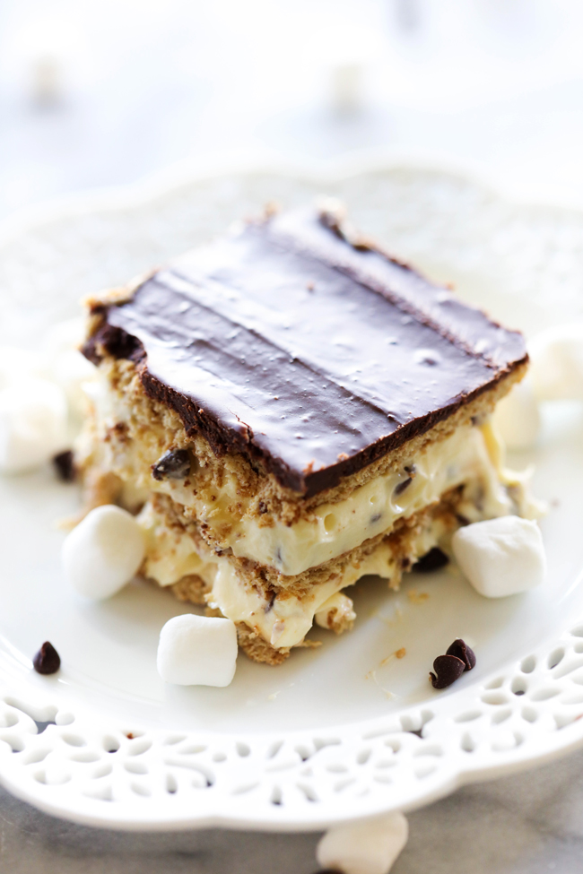 This No Bake S'more Eclair Cake is so easy and is loaded with everything you love about s'mores! The graham crackers soften perfectly to create one mouth watering bite after another! Loaded with marshmallows, chocolate chips, chocolate frosting and graham crackers- this is sure to be a hit wherever it goes!