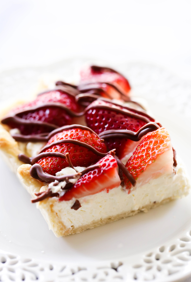 This Strawberry Cream Slab Pie is the PERFECT summertime dessert! The strawberries are beautifully topped on a cream pie and drizzled with chocolate. This is a great dessert for feeding a crowd and is ALWAYS a hit!