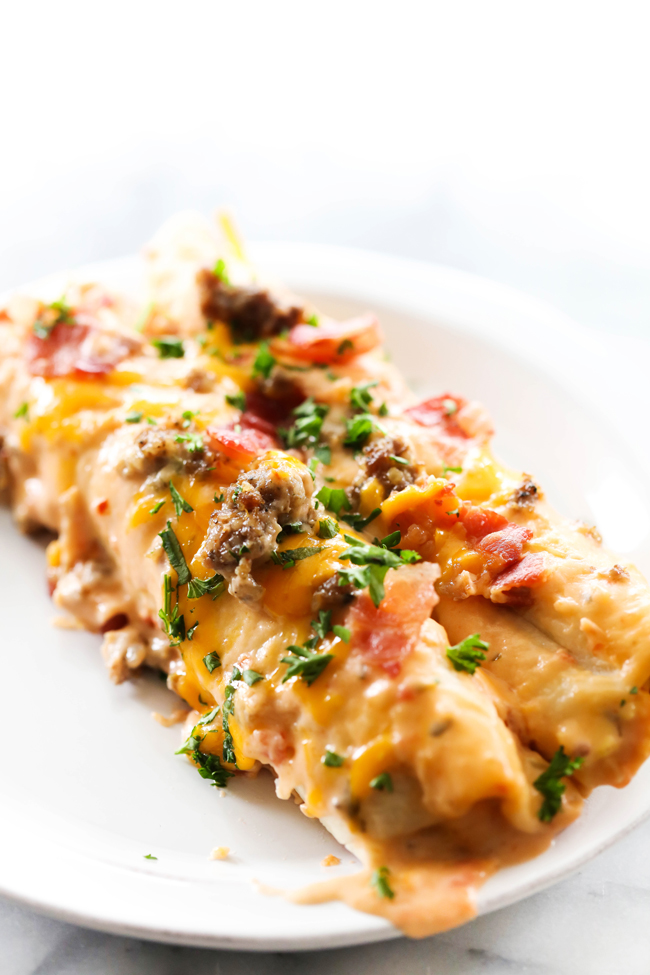 These Breakfast Enchiladas are super filling and packed with flavor. This recipe combines so many breakfast favorites like eggs, bacon and sausage and transforms them into a new way to enjoy them. It is sure to become a new breakfast regular and family favorite.
