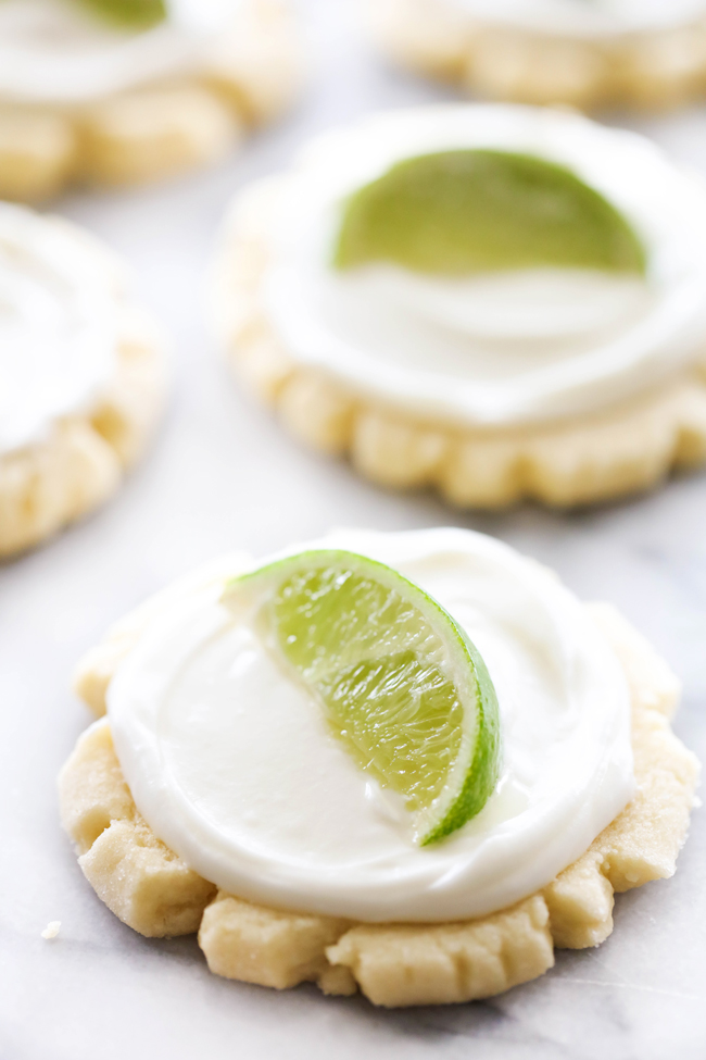 Coconut Lime Sugar Cookies with coconut lime frosting and garnished with a slice of lime.