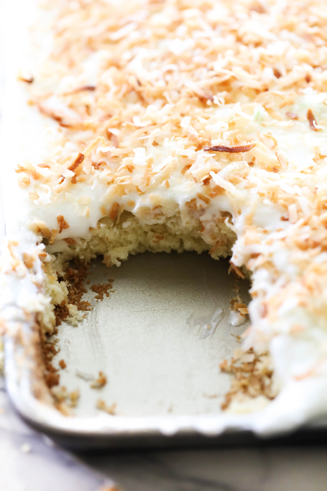 Coconut Lime Sheet Cake garnished with toasted coconut in a baking sheet with corner piece removed.
