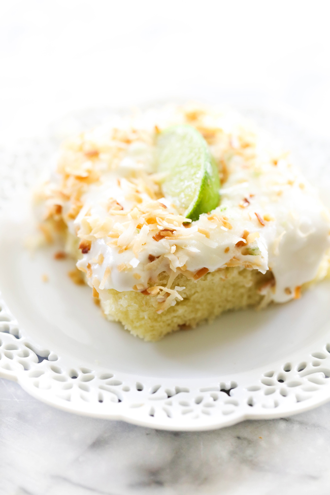 Slice of Coconut Lime Sheet Cake garnished with toasted coconut and a slice of lime on a white plate.