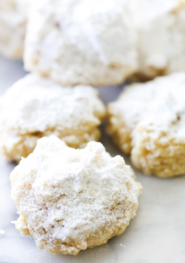 Cheesecake Cookies dusted with powdered sugar on marble slab.