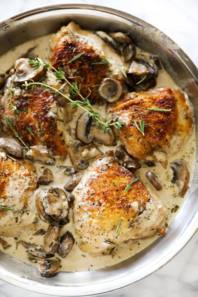 Creamy Garlic Herb Chicken garnished with fresh rosemary in a stainless steel skillet.