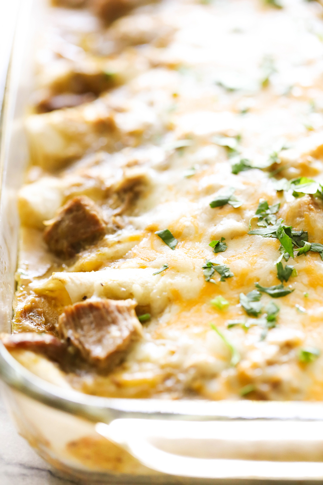 Chile Verde Pork Enchiladas topped with cheese and fresh chopped cilantro in clear baking dish.