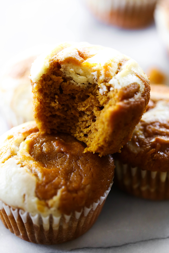 Pumpkin Cream Cheese Muffins stacked with a bite taken out of top muffin.