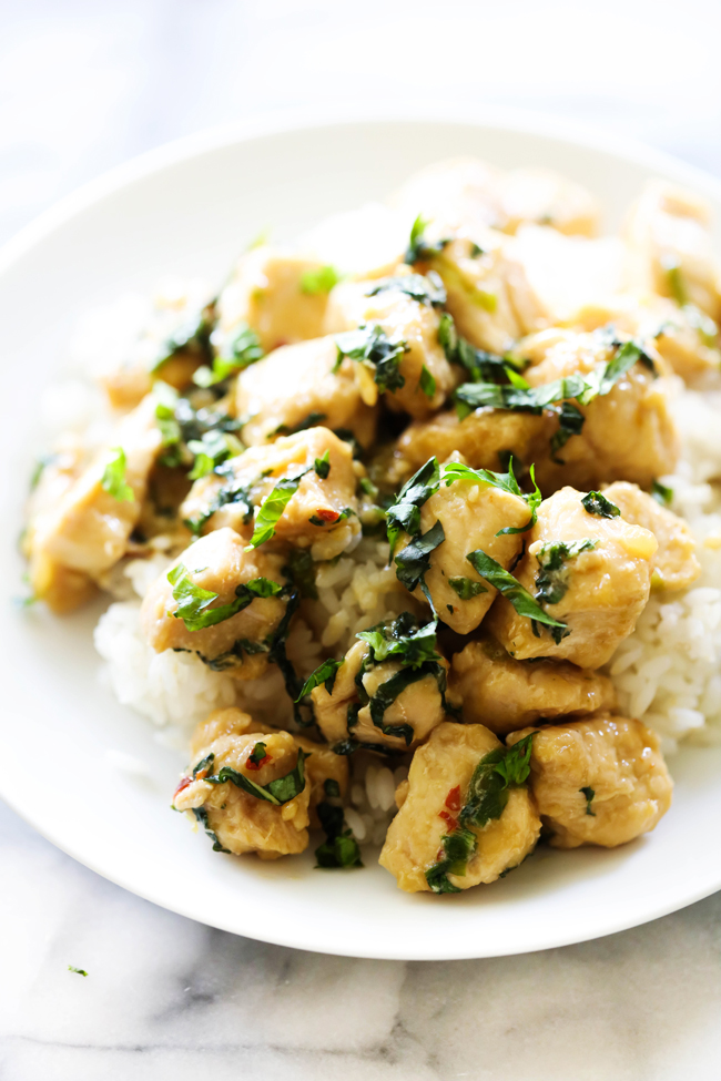 Spicy Basil Chicken served over white rice and garnished with fresh chopped basil on white plate.
