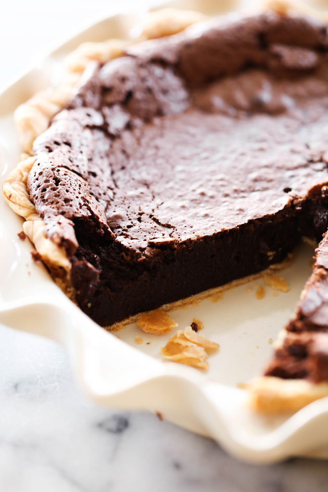 Brownie Pie in white pie pan with slice removed.