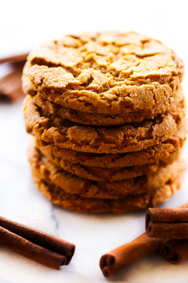 Crisp Gingersnaps cookies stacked with cinnamon sticks surrounding them.