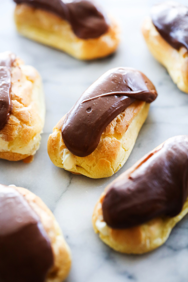 Homemade Eclairs with chocolate frosting displayed on marble slab.