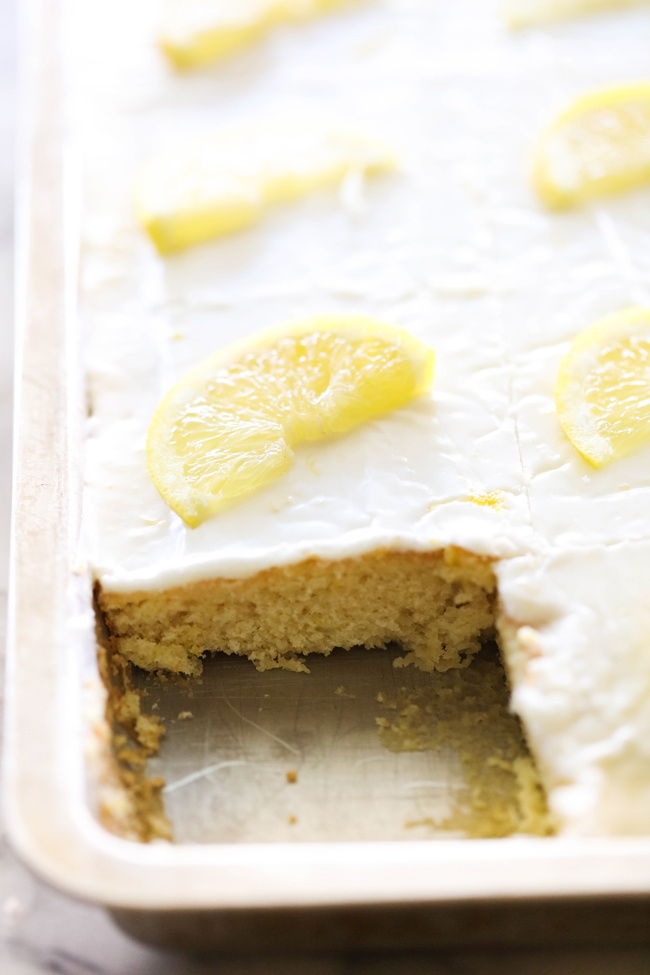 Lemon Sheet Cake in a baking sheet garnished with lemon slices with a slice of cake removed.