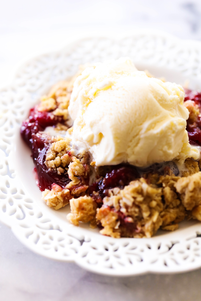 A serving of Cherry Crisp with a scoop of vanilla ice cream on top on a white plate.