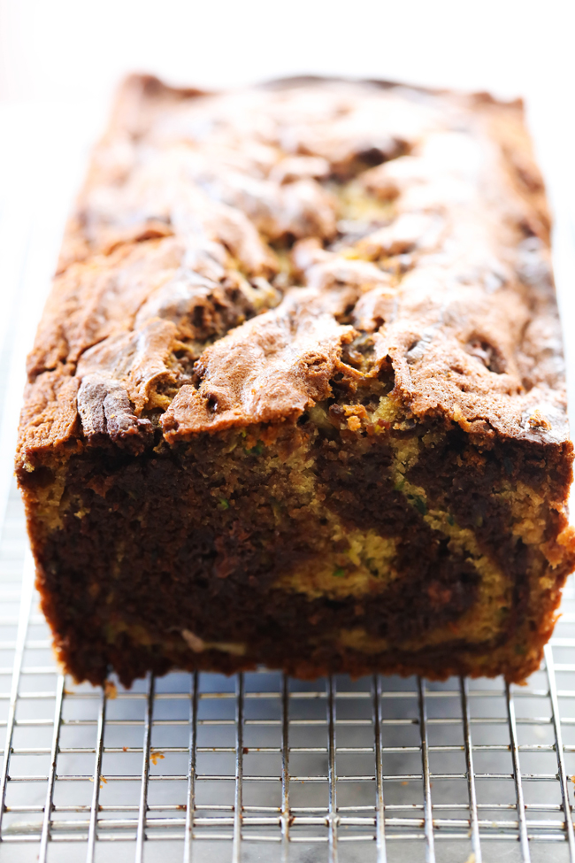 Chocolate Swirl Banana Zucchini Bread loaf on a cooling rack cut open to see the swirl inside.