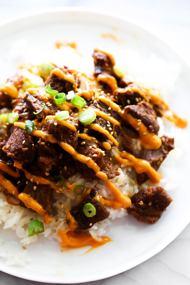 Korean Beef Bulgogi on a white plate with Gochujang Mayo drizzled over the top and garnished with green onions and sesame seeds.