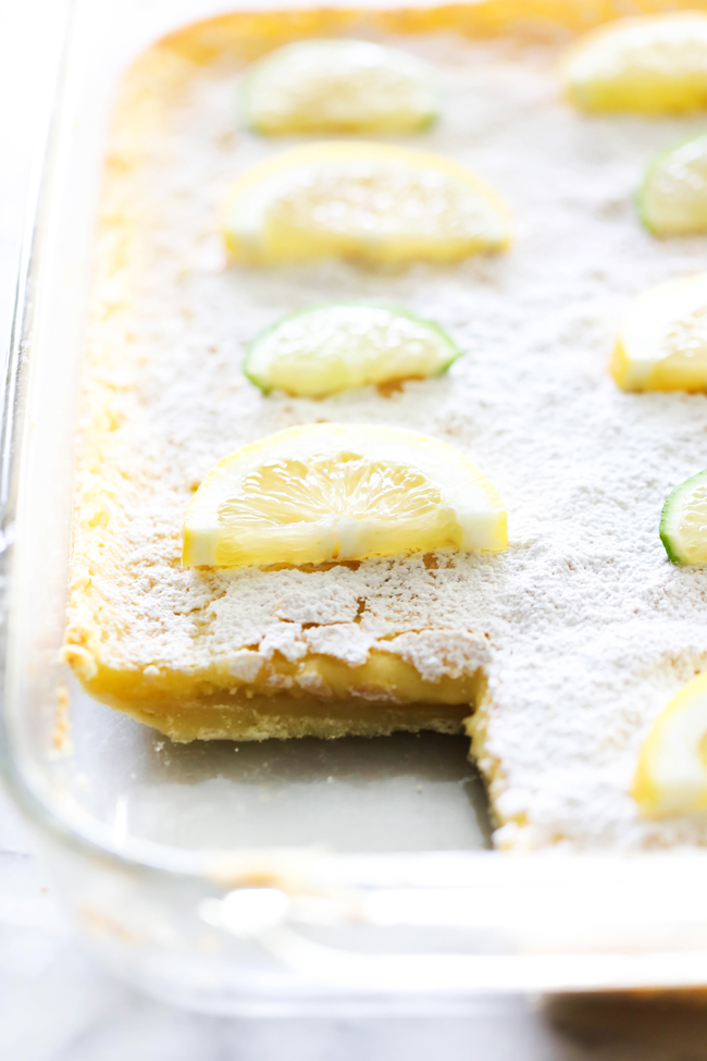 Lemon Lime Bars in a clear baking dish with corner slice removed.